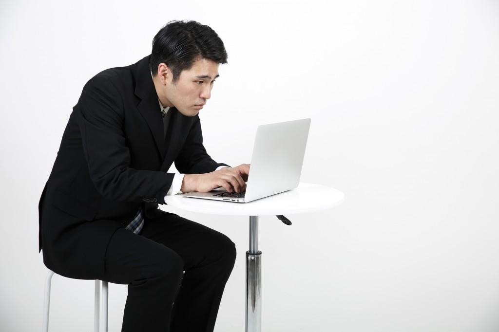 前のめりになってパソコンをしている男性