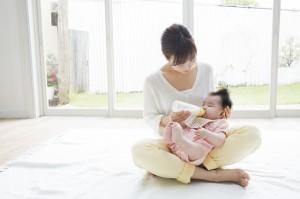 あぐらスタイルで授乳する産後の女性